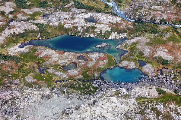 A pair or barely-separated alpine lakes in the tundra playground beyond the end of the trail.