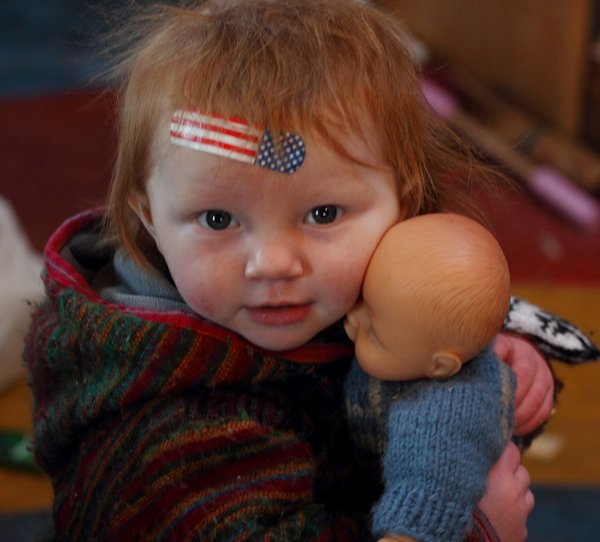 Lituya sporting a patriotic bandaid after a brief encounter with the woodstove, hugging her doll.