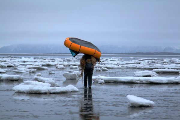 Hig carries his packraft across the icy tide flats at Controller Bay.