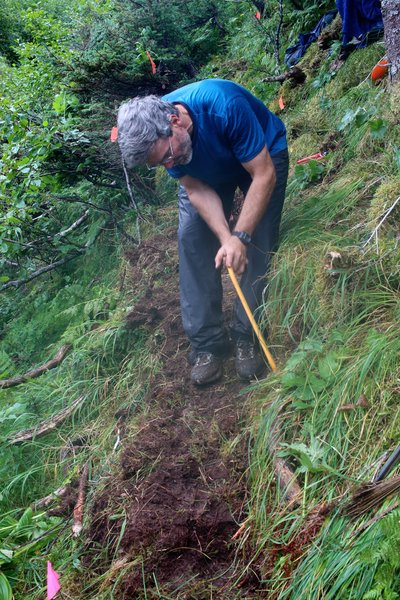 Randy Weist uses a bow saw to trim roots hanging into the trail.