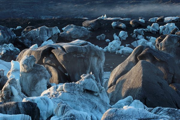 Mist and sunlight hit the stranded bergs of Oily Lake on a chilly dawn.  This ice-dammed lake can drain out underneath Malaspina Glacier, leaving icebergs stranded on glacial silt.