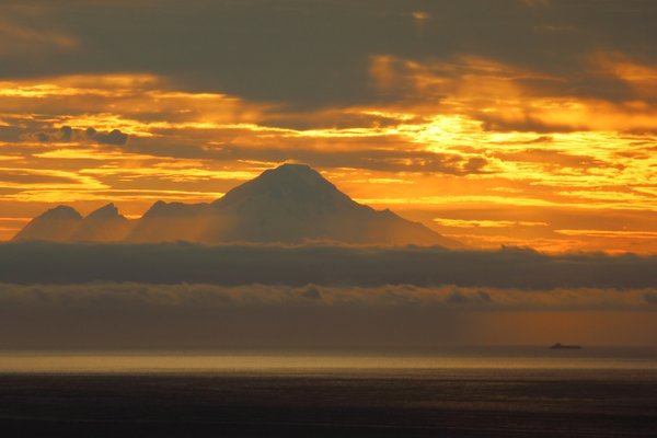 A small cargo vessel - perhaps a oil tanker - makes its way up Cook Inlet.