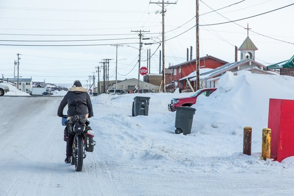 Kim rides into Kotzebue. Cars and stop signs are a stark contrast to the world we'd just ridden from