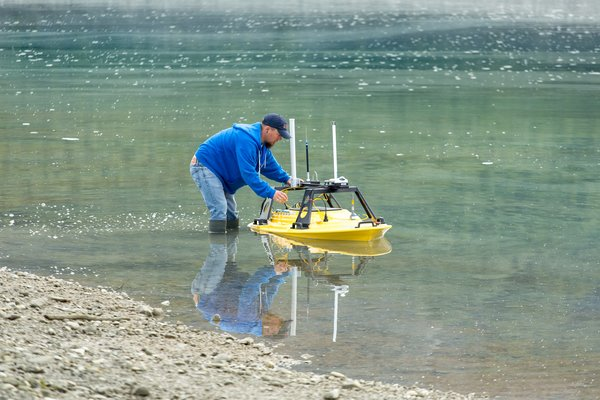 A geology student holds onto the several hundred thousand dollar, marine survey, remote control boat while the final preparations are conducted, before the first mapping survey.