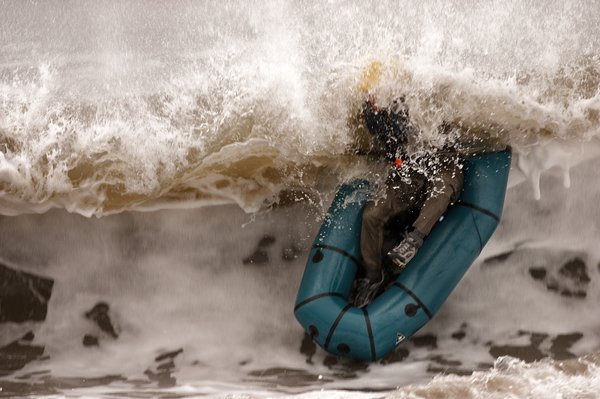 After the wave broke, the packraft popped to the surface, upside down.  Moments later Andrew followed and clambered back in.