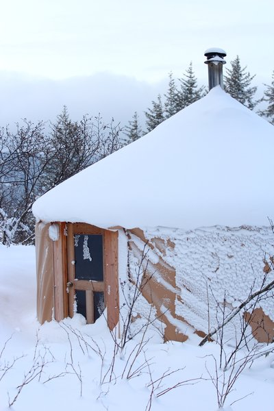 snow slowly accumulates on the roof of the guest yurt