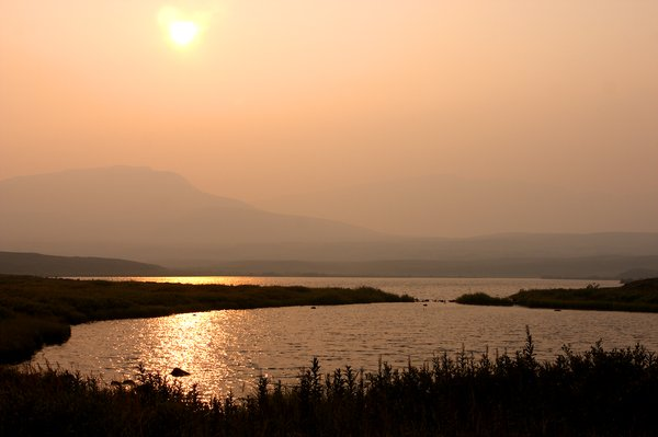 The sun sets in a pink haze of forest fire smoke. Looking west towards Groundhog Mountain.