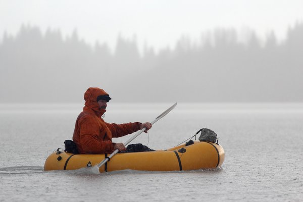 Carl Donnely paddles in the rain in a packraft.