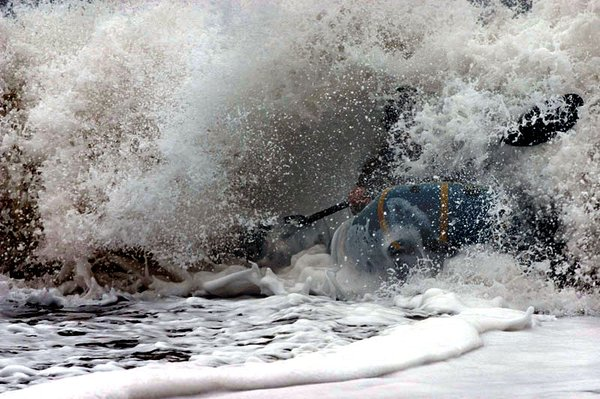 Hig surfs out of a breaking wave at the mouth of the Queets River in Washington