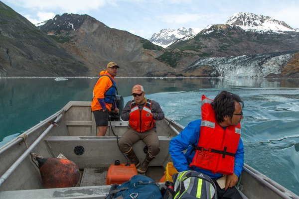 A three-person team takes a skiff ride near the landslide in upper Taan Fjord. A total of fourteen people, from various earth science backgrounds, joined the main summer expedition to study the landslide and tsunami, which occurred in October 2015.